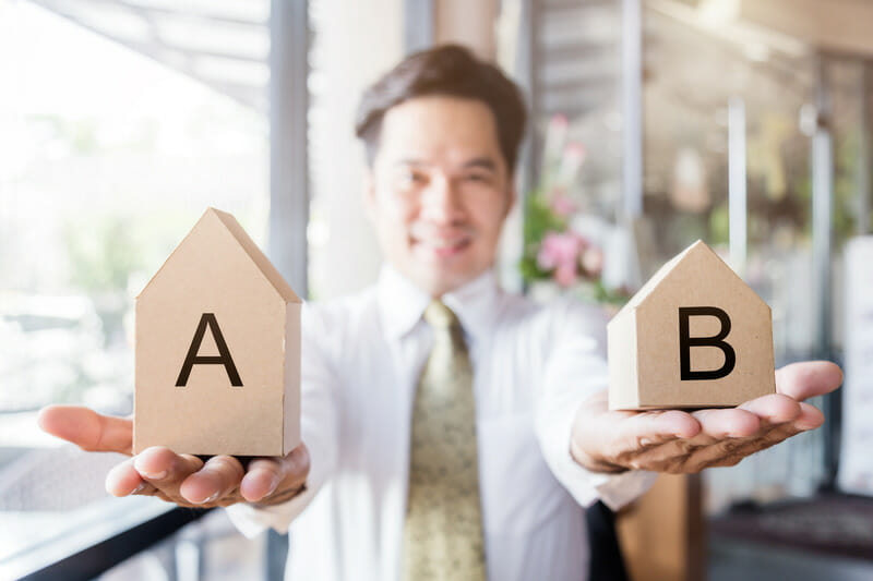 house home mortgage  concept with business man hand with house model and sample of material on wooden desk